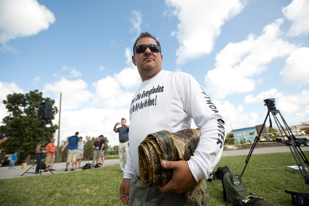 ". Trapper ""Python Dave\"" Leibman holds a roll of snake skins he is selling at the Python Challenge kick-off in Davie, Fla. (AP Photo/J. Pat Carter)"