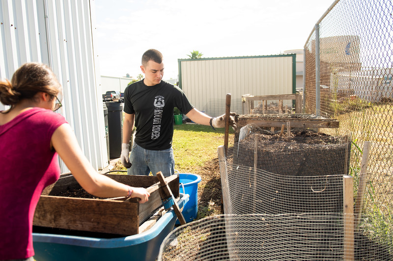 Students Mark Rolph and Christina Ballouz volunteer at the Islander Green Garden by sifting through compost.
