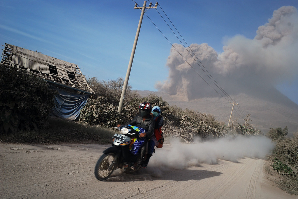 . Residents flee on motorcycle from the eruption of Mount Sinabung volcano seen from Karo district on October 9, 2014.  AFP PHOTO / Sutanta  ADITYA/AFP/Getty Images
