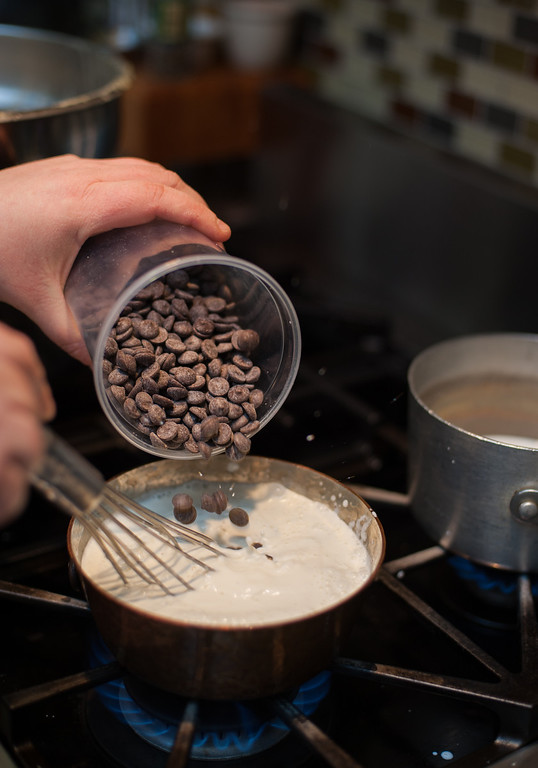 . Emma Currie adds chocolate chips to heavy cream to make chocolate fondue at the Market on Main in downtown Mt. Pleasant. (Sun photo by Holly Mahaffey/@hollymahaffey)