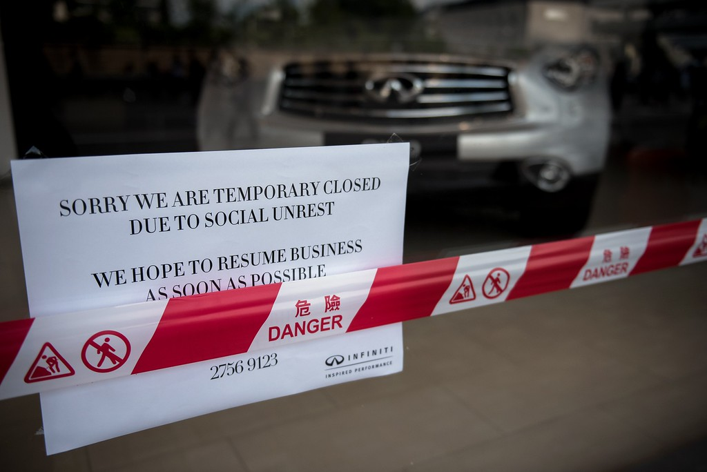 ". A sign announces that a Infiniti car dealership is closed temporarily ""due to social unrest\"" during pro-democracy protests in Hong Kong on October 1, 2014. Hong Kong has been plunged into the worst political crisis since its 1997 handover as pro-democracy activists take over the streets following China\'s refusal to grant citizens full universal suffrage.  Alex Ogle/AFP/Getty Images"