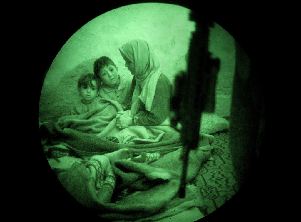. A U.S. Marine guards an Iraqi mother and children while other Marines interrogate the father while on a search operation for insurgents in the early hours of February 1, 2007 in Ramadi in Iraq\'s Anbar province. American forces use night vision goggles, taking advantage of technology to aid the element of surprise and reduce the effectiveness of insurgent snipers on U.S. forces. (Photo by John Moore/Getty Images)