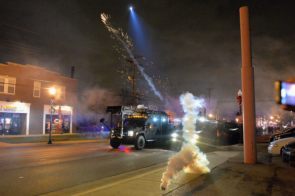 . Police fire canisters of tear gas as demonstrators protest the death of 18-year-old unarmed black teenager Michael Brown, who was shot to death by a white police officer, in Ferguson on November 24, 2014. Protesters set buildings ablaze and looted stores in the US town of Ferguson on November 24 after a grand jury chose not to press charges against a white officer who shot dead a black teen. AFP PHOTO/Michael B. ThomasMichael B. Thomas/AFP/Getty Images