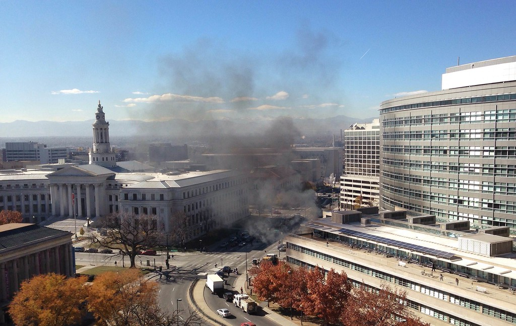 . Smoke rises from an apparent car fire on 14th Street just north of Colfax Avenue near the Wellington Webb city office building in downtown Denver, Thursday, Nov. 7, 2013. (Daniel J. Schneider, The Denver Post)