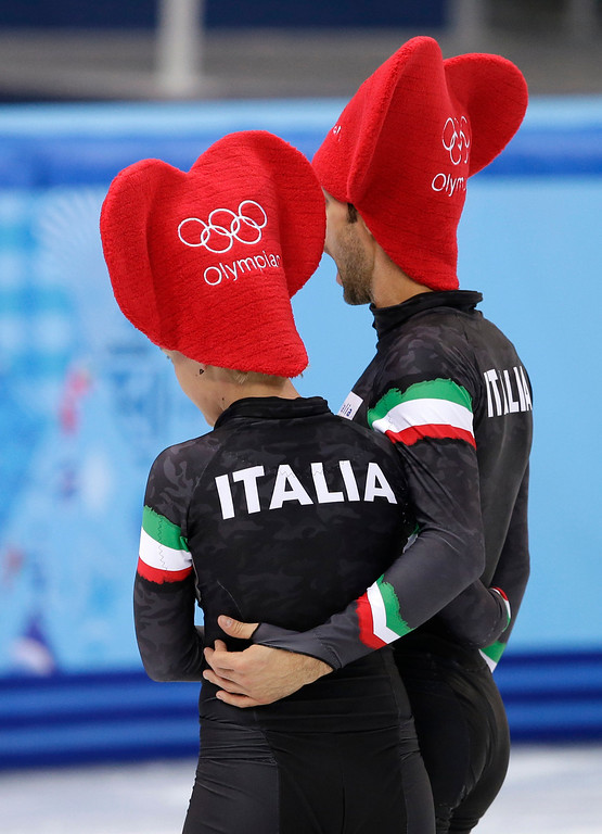 . Arianna Fontana of Italy and Anthony Lobello of Italy wear Valentines Day themed hats during a short track speedskating practice session at the Iceberg Skating Palace during the 2014 Winter Olympics, Friday, Feb. 14, 2014, in Sochi, Russia. (AP Photo/Darron Cummings)
