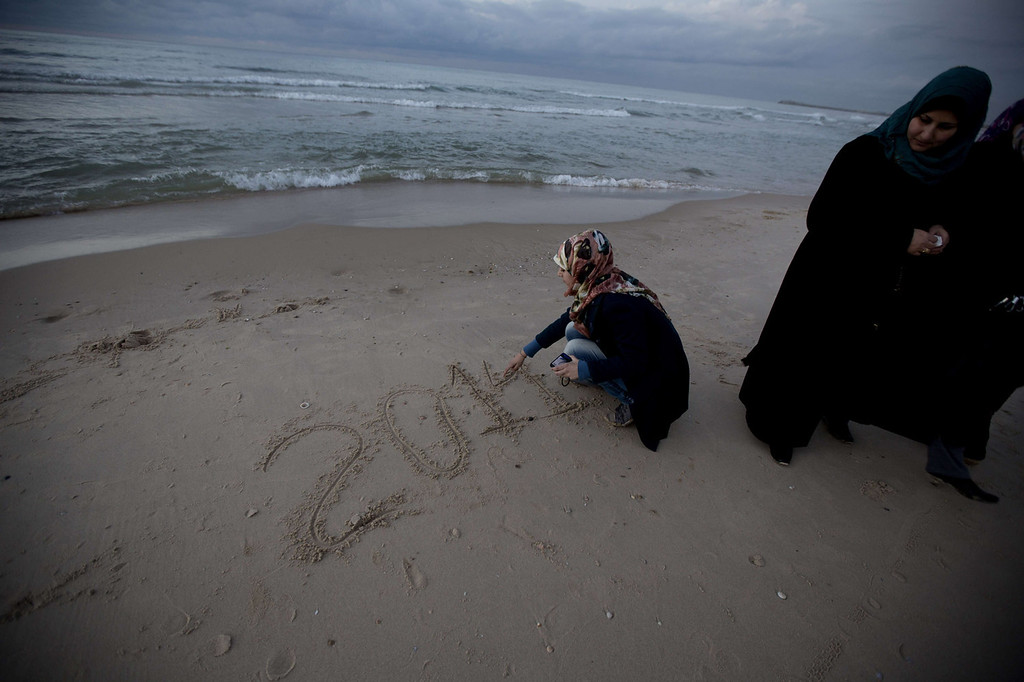 . A Palestinian girl writes in the sand 2014 during the last sunset of the year in Gaza City on December 31, 2013. MOHAMMED ABED/AFP/Getty Images