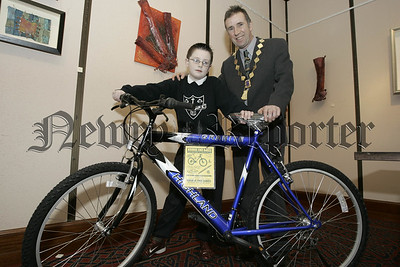 Newry Lions Club Sponsored swim awards. President William Hanna presents Ros McGivern from Cloughoge P.S. who won a bicycle in the grand draw. 06W7N15