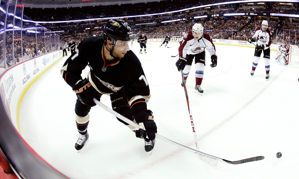 . Anaheim Ducks center Andrew Cogliano, left, battles Colorado Avalanche center John Mitchell for the puck during the second period of a NHL hockey game in Anaheim, Calif., Sunday, Feb. 24, 2013. The Ducks won 4-3 in overtime. (AP Photo/Chris Carlson)