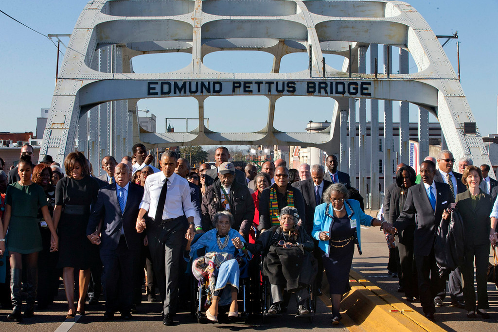 ". ADDS NAME OF SECOND WOMAN IN WHEELCHAIR - President Barack Obama, fourth from left, walks holding hands with Amelia Boynton Robinson, who was beaten during ""Bloody Sunday,\"" as they and the first family and others including Rep. John Lewis, D-Ga, left of Obama, walk across the Edmund Pettus Bridge in Selma, Ala,. for the 50th anniversary of the landmark event of the civil rights movement, Saturday, March 7, 2015. At far left is Sasha Obama and at far right is former first lady Laura Bush. Adelaide Sanford also sits in a wheelchair. (AP Photo/Jacquelyn Martin)"