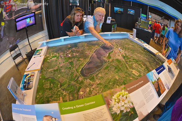 A woman points out where the dredging operations are taking place on the map of Onondaga Lake in the Center of Progress building at The Great New York State Fair in Syracuse, New York.