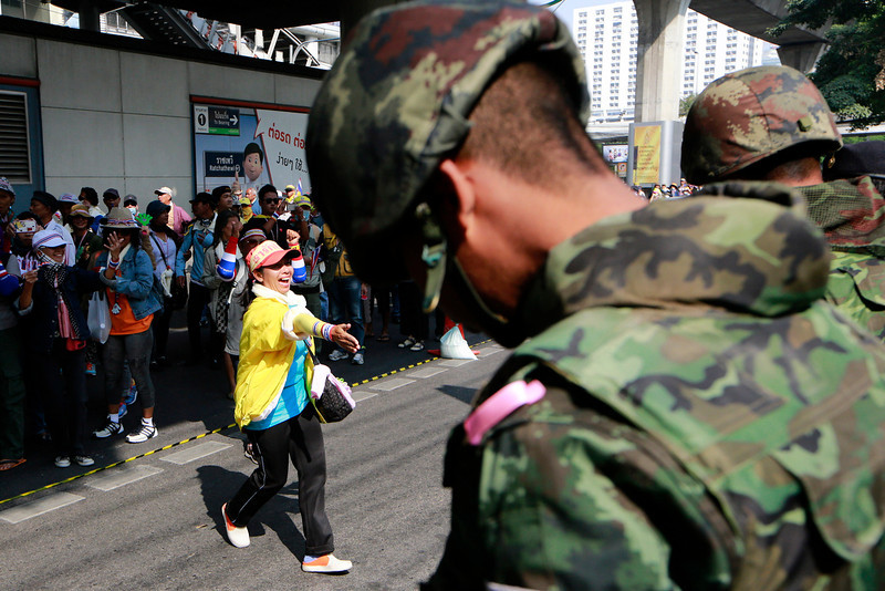 . An anti-government protester offers a handshake with Thai soldiers while marching on the street during a rally Wednesday, Jan. 22, 2014 in Bangkok, Thailand. Gunmen shot and wounded a top leader of a major pro-government movement in northern Thailand on Wednesday, and demonstrators pushing to overthrow the prime minister defied the start of a state of emergency imposed in the capital to cope with the nation\'s increasingly bloody political crisis. (AP Photo/Wason Wanichakorn)