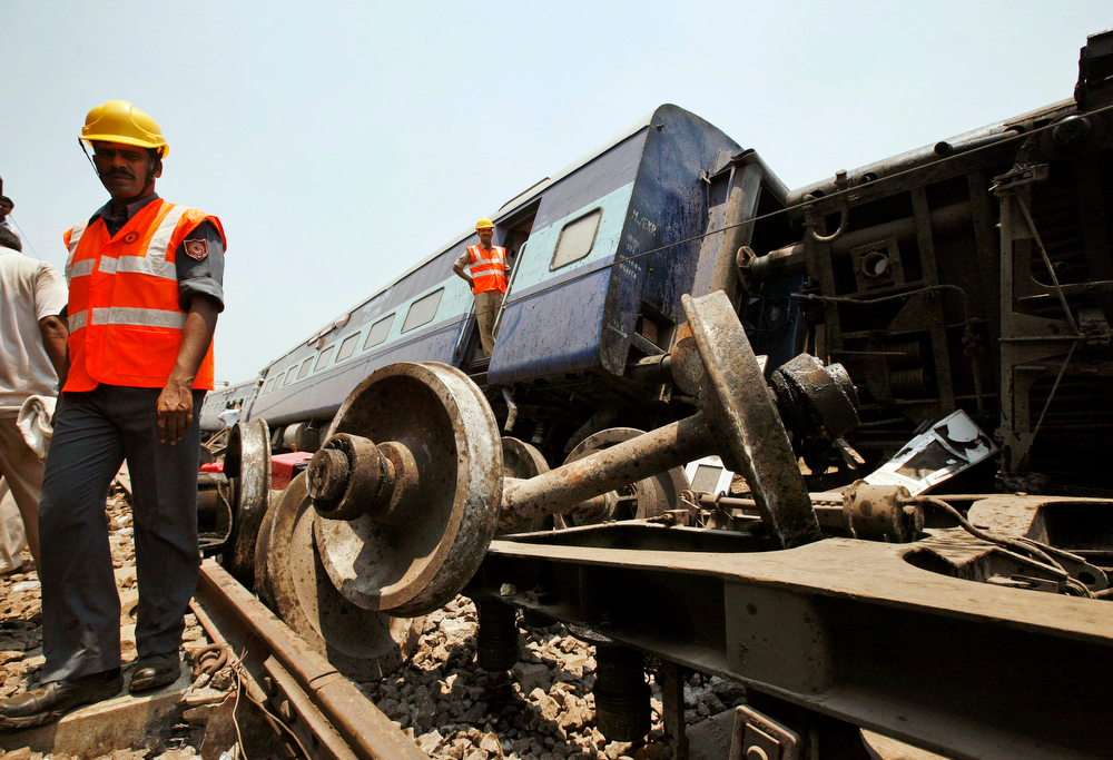 Description of . Indian rescue workers gather at the site of a train accident near in Sitheri near Arakkonam, India, Wednesday, April 10, 2013. A passenger train traveling through southern Indian derailed at Sitheri, about 90 kilometers (56 miles) southwest of Chennai early Wednesday morning, killing one person and injuring dozens more, according to local reports. (AP Photo/Arun Sankar K.)