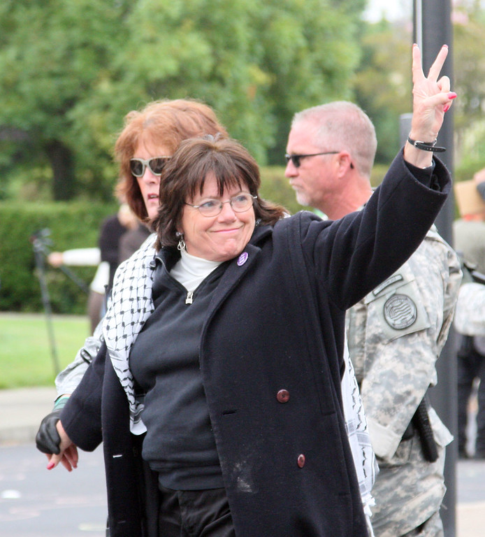 . Sherri Maurin flashes the peace sign while being arrested in Livermore, Calif. on Tuesday, Aug. 6 2013, by an officer from LLNL Protective Forces at a protest of nuclear weapons at the lab on the 68th anniversary of the atomic bombings of Hiroshima and Nagasaki during WWII.  (Jim Stevens/Bay Area News Group)