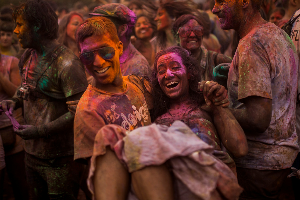 . A man carries a woman as revelers throw special colored powders over each other, during a Monsoon Holi Festival in Madrid, Spain, Saturday, Aug. 9, 2014.(AP Photo/Andres Kudacki)