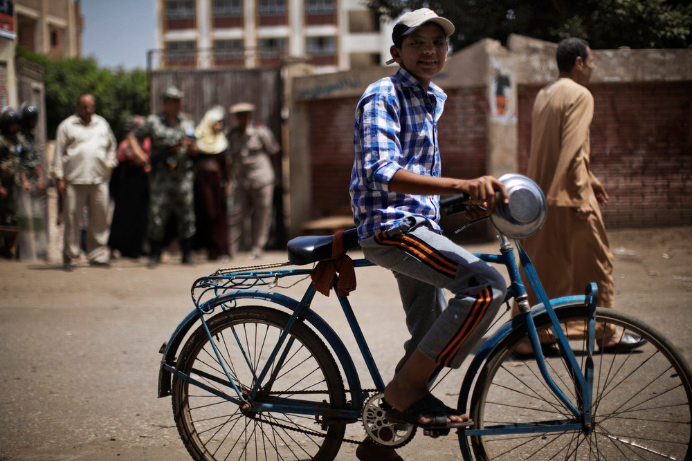 . An Egyptian boy rides a bicycle past a polling station in the village of Namul, 60 kms north of Cairo, on the second day of the country\'s landmark presidential election on May 24, 2012. Egyptians swarmed polling stations on the second day of a gripping presidential election in which candidates are pitting stability against the ideals of the uprising that ended Hosni Mubarak\'s rule. MARCO LONGARI/AFP/Getty Images
