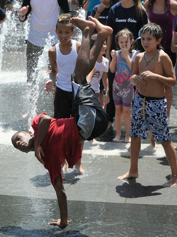 . A young man dances in the fountain plaza during the 5th Annual National Dance Day celebration at Grand Park. The event stretched from Grand Part to The Music Center. More than 2,000 people participated in the free all-day dance extravaganza.  Los Angeles CA. 7/25/2014(Photo by John McCoy Daily News)