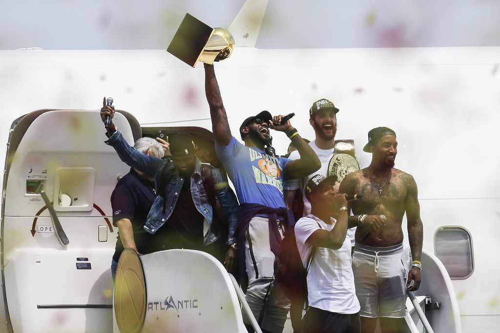 . Cleveland Cavaliers\' Lebron James, center, holds up the NBA Championship trophy alongside teammates Kyrie Irving, left, Kevin Love, rear right, J.R. Smith, right, and Tristan Thompson, front,   at the airport in Cleveland, Monday, June 20, 2016. (AP Photo/John Minchillo)