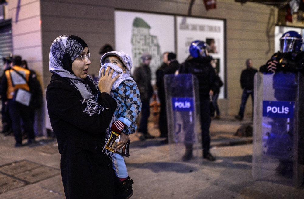 . A woman tries to protect her baby from tear gas during clashes between riot-police and protestors after the funeral of Berkin Elvan, the 15-year-old boy who died from injuries suffered during last year\'s anti-government protests, in Istanbul on March 12, 2014. Riot police fired tear gas and water cannon at protestors in the capital Ankara, while in Istanbul, crowds shouting anti-government slogans lit a huge fire as they made their way to a cemetery for the burial of Berkin Elvan. (BULENT KILIC/AFP/Getty Images)