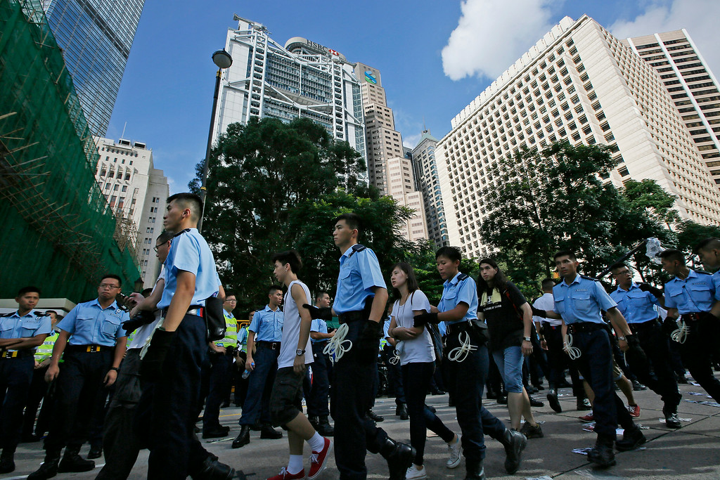 . Arrested protesters are escorted out by police officers outside HSBC headquarters in the financial district in Hong Kong Wednesday, July 2, 2014, following a huge rally to show their support for democratic reform and oppose Beijing\'s desire to have the final say on candidates for the chief executive\'s job. More than 500 protesters were arrested from sit-in during pro-democracy rally. (AP Photo/Vincent Yu)