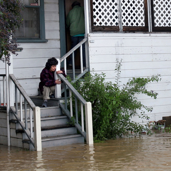 Carol Mendez sits on the porch of her flooded Clinton Street home, that she shares with Bob Reynolds, rear, in Napa, Calif, Saturday Dec. 31, 2005.   Reynolds is a 50-year resident of Napa. (AP Photo/Dino Vournas)