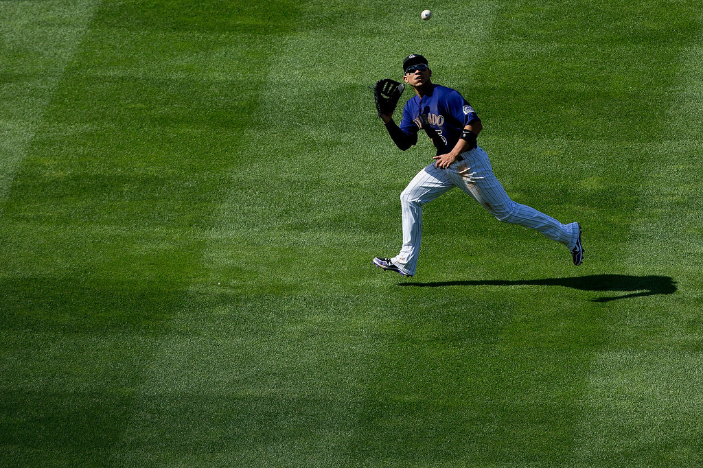 . Left fielder Carlos Gonzalez #5 of the Colorado Rockies makes a catch on the run for the third out of the seventh inning against the Chicago Cubs at Coors Field on July 21, 2013 in Denver, Colorado. The Rockies defeated the Cubs 4-3.  (Photo by Justin Edmonds/Getty Images)