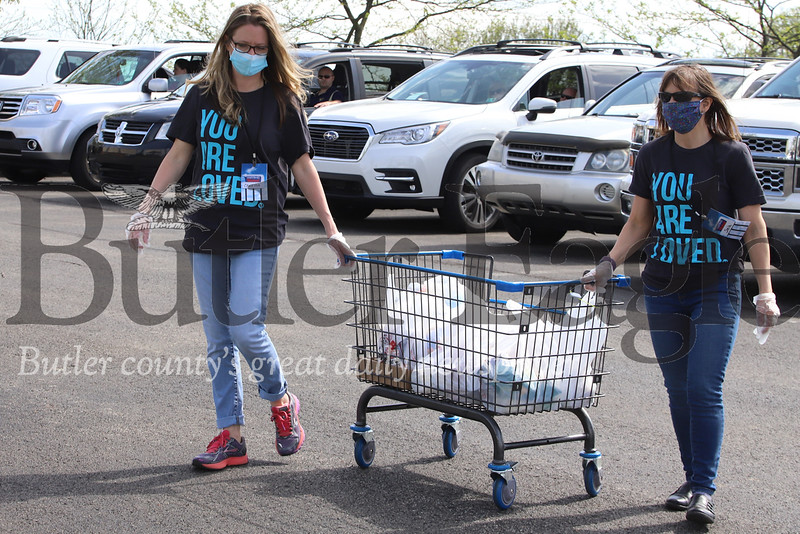 Victory Family Church in Cranberry members Sheila Neely (right) and Carissa Palamides go from car to car collecting food donations during the church's drive-in service Saturday. Seb Foltz/Butler Eagle