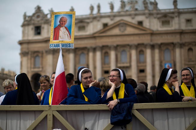 . A portrait of late Pope Pope John Paul II is held up by Polish nuns in front of St. Peter\'s Basilica at the Vatican, Saturday, April 26, 2014. Pilgrims and faithful are gathering in Rome to attend Sunday\'s ceremony at the Vatican in which Pope Francis will elevate in a solemn ceremony John XXIII and John Paul II to sainthood. (AP Photo/Emilio Morenatti)