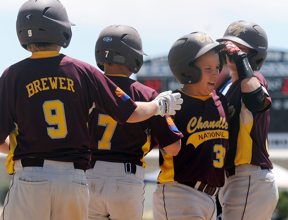 . (Will Lester/Inland Valley Daily Bulletin) Arizona\'s Kyle Hasler (second from right) is congratulated by teammates after hitting a 3-run home run in the first inning against Hawaii Wednesday. Chandler Little League, from Chandler, Arizona, eliminates Central East Maui, from Hawaii, with a 5-3 win Wednesday August 7, 2013 11-3 at the Little League Western Regional Tournament at Al Houghton Stadium in San Bernardino.