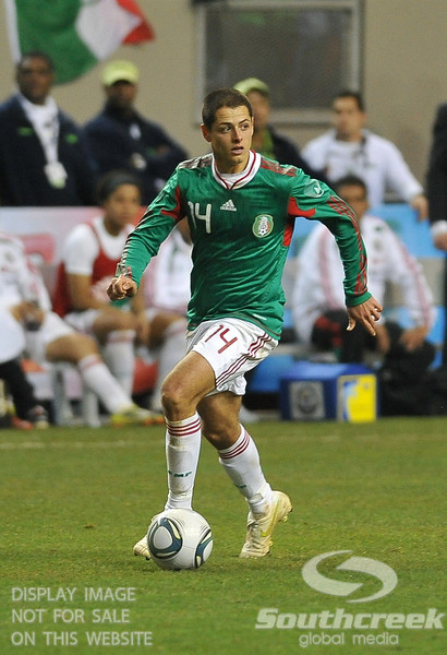 Mexico's Forward Javier Hernandez (#14) dribbles the ball in Soccer action between Bosnia-Herzegovina and Mexico.  Mexico defeated Bosnia-Herzegovina 2-0 in the game at the Georgia Dome in Atlanta, GA.