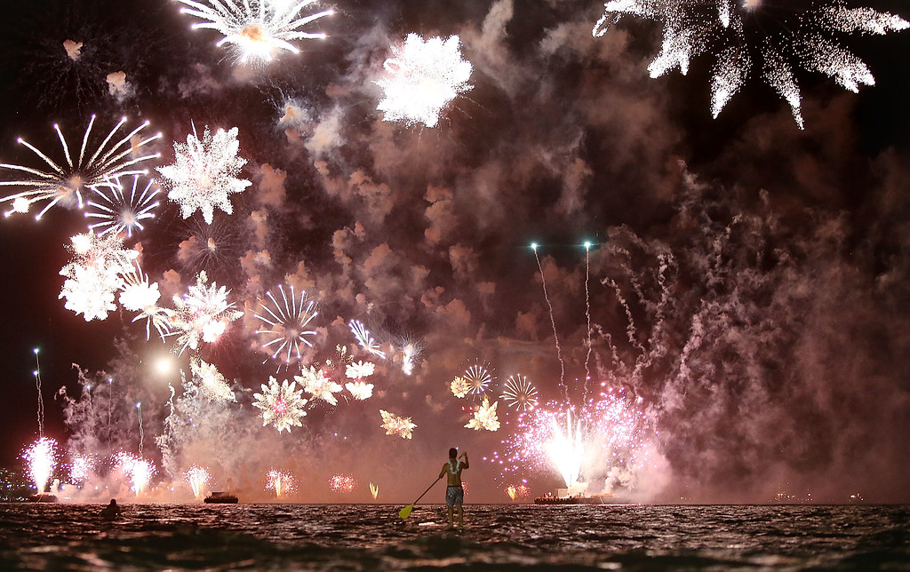 . A man rides a stand up paddle board as fireworks explode above him during New Year\'s festivities on Copacabana Beach on January 1, 2015 in Rio de Janeiro, Brazil. Up to 2 million revelers were expected on Copacabana Beach to watch the annual New Year\'s fireworks display which this year coincided with the start of the city\'s 450th anniversary celebrations.  (Photo by Mario Tama/Getty Images)