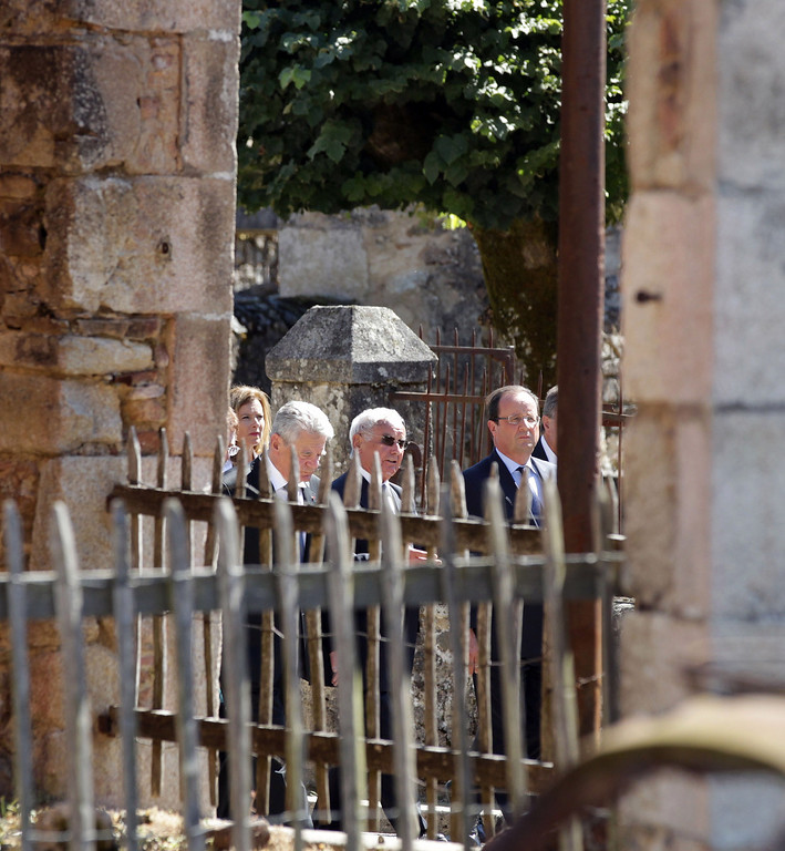 . French President Francois Hollande (R) and his German counterpart Joachim Gauck (L) visit the ruins of the town on September 4, 2013 with Robert Hebras (C), 88, one of the last survivors of the World War II massacre in Oradour-sur-Glane and the town\'s mayor Raymond Frugier (R). The town has become a ghostly war crimes museum since Nazi troops burnt it to the ground on June 10, 1944. Six hundred and forty-two original inhabitants were massacred in Oradour and no one knows exacty why. Women and chldren were massacred in the church before their bodies were burnt by a German SS division. Hebras is one of three survivors still alive. ROMAIN PERROCHEAU/AFP/Getty Images
