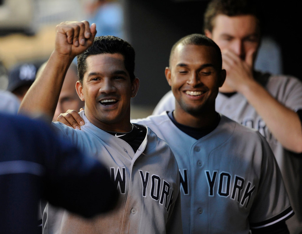 . (R) Zoilo Almonte #45 of the New York Yankees congratulates teammate Alberto Gonzalez #40 on scoring a run against the Minnesota Twins during the fifth inning. (Photo by Hannah Foslien/Getty Images)