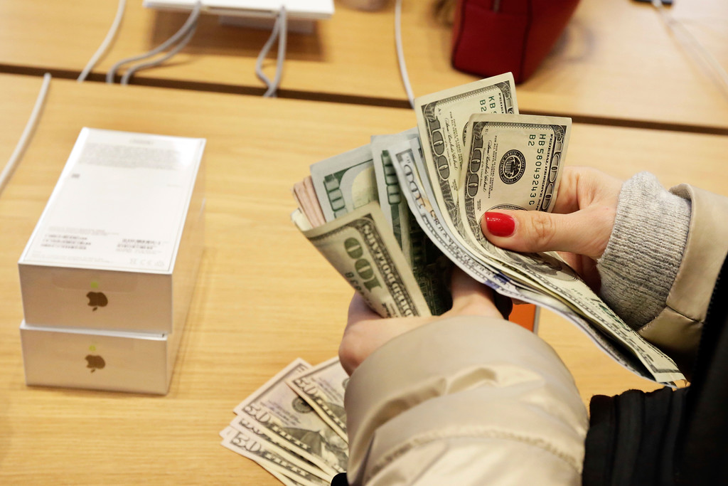 . A customer counts out cash for the purchase of two iPhone X\'s at the Apple Store on New York\'s Fifth Avenue, Friday, Nov. 3, 2017. (AP Photo/Richard Drew)