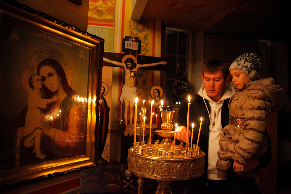. A Russian Orthodox believer lights candles during a Christmas mass in a church in Grozny, Russia, late Sunday, Jan. 6, 2013. Christmas falls on Jan. 7 for Orthodox Christians in the Holy Land, Russia and other Orthodox churches that use the old Julian calendar instead of the 16th-century Gregorian calendar adopted by Catholics and Protestants and commonly used in secular life around the world. (AP Photo/Musa Sadulayev)