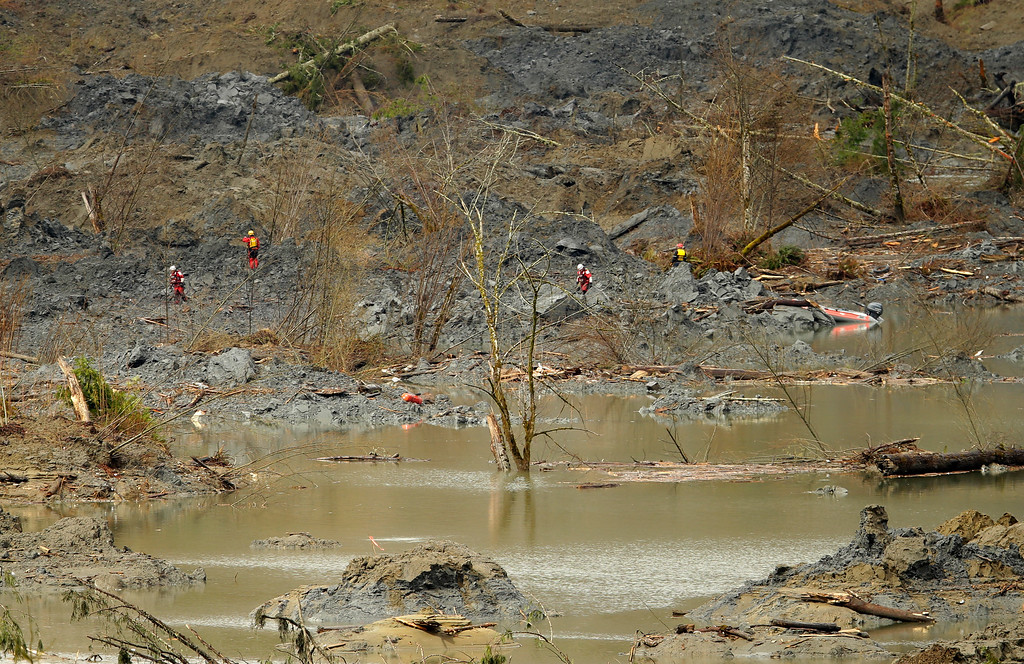 . Search workers wearing red are dwarfed by the mud and debris filled landscape they are searching Thursday, March 27, 2014, where a massive mudslide struck Saturday near Darrington, Wash. The searchers shown had to use a boat to reach the area shown. (AP Photo/Ted S. Warren, Pool)