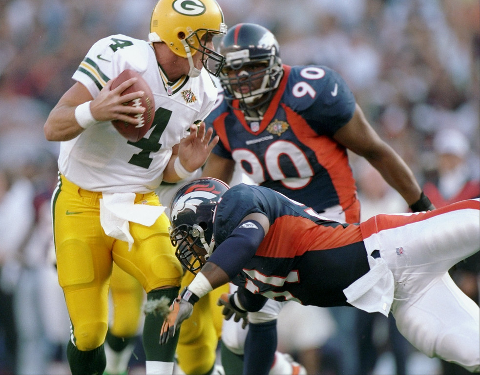 . Brett Favre #4 of the Green Bay Packers avoids being sacked by John Mobley #51 and Neil Smith #90 of the Denver Broncos during Super Bowl  XXXII at Qualcomm Stadium in San Diego, California.  (Andy Lyons/Allsport)