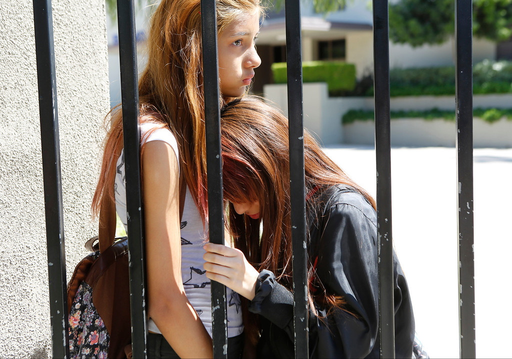 . High school students, Jazmine Villalobos, 14, left, and Michelle Lopez, 14, react after learning the death of senior student AdrianCastro, as they leave El Monte High School in El Monte, Calif., Friday, April 11, 2014. Adrian Castro, an El Monte High School senior, was on the Humboldt State University-bound bus that crashed in Orland on Thursday, an El Monte school official said. (AP Photo/Damian Dovarganes)