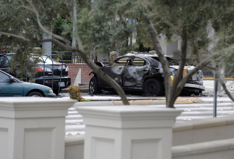 . A burned taxi cab sits at the site of what is being described as a gun battle between shooters in two vehicles along the Las Vegas Strip on February 21, 2013 in Las Vegas, Nevada. According to reports gunshots were fired between black SUV at a Maserati, causing the Maserati to crash into a taxi, that burst into flames. Five vehicles were involved in the subsequent crash with the Maserati driver and two people in the taxi being killed.  (Photo by David Becker/Getty Images)