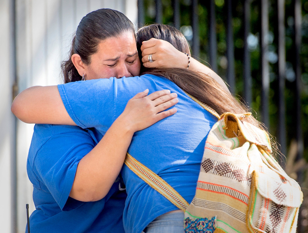 . An El Monte High School staff member hugs a distraught student after two female classmates were hospitalized and a male student is unaccounted for when a bus carrying students to a Humbolt State University campus tour collided head on with a FedEx big rig in Northern California April 10, 2014.  (Staff photo by Leo Jarzomb/San Gabriel Valley Tribune)