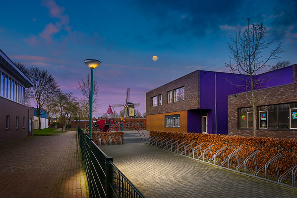Fine Art architectuur foto van basisschool De Beekgraaf met speelplaats en fietsenrekken met molen De Windlust en Sporthal De Overbeek te Nistelrode in de winter bij maanlicht.
