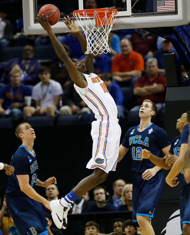 . Florida forward Dorian Finney-Smith (10) shoots against UCLA forward Travis Wear (24) and UCLA forward David Wear (12) during the first half in a regional semifinal game at the NCAA college basketball tournament, Thursday, March 27, 2014, in Memphis, Tenn. (AP Photo/John Bazemore)