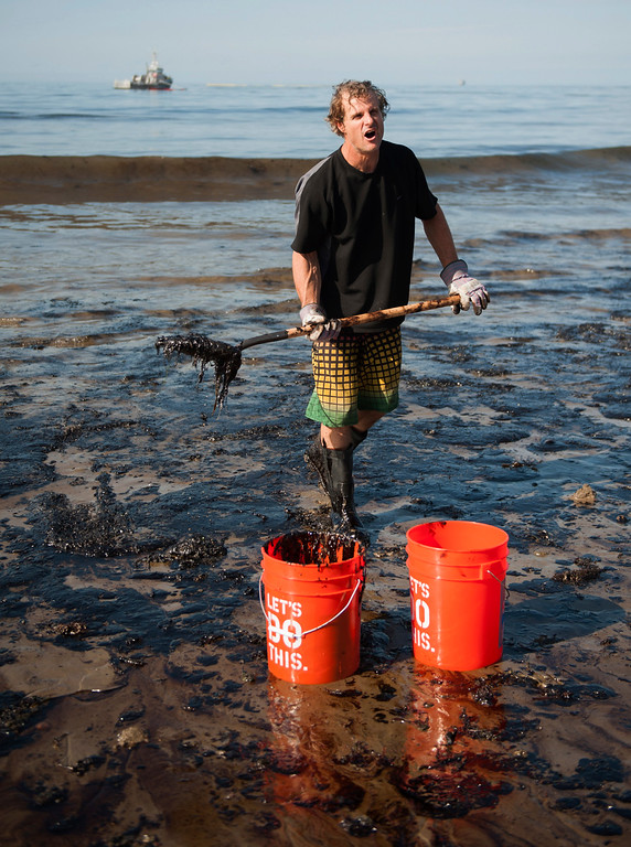 . A man shovels up oil on a section of beach about a mile east of Refugio State Beach, Calif., Wednesday, May 20, 2015. A broken onshore pipeline spewed oil down a storm drain and into the ocean for several hours Tuesday before it was shut off. (Kenneth Song/The News-Press via AP)