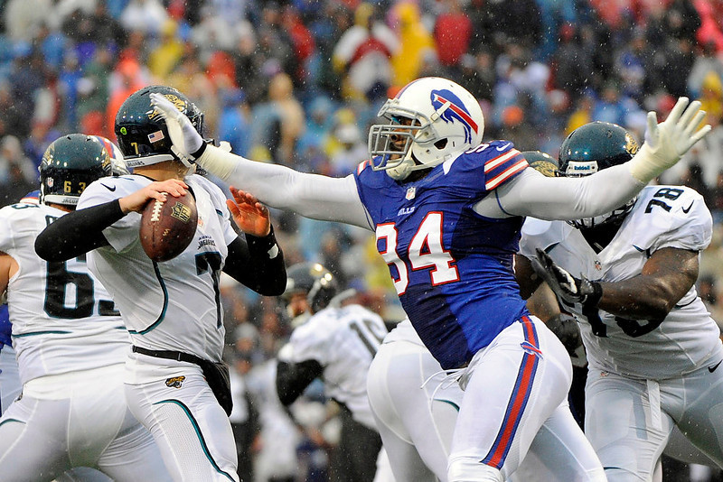 . Buffalo Bills defensive end Mario Williams (94) knocks the ball away from Jacksonville Jaguars\' Chad Henne (7) during the first half of an NFL football game on Sunday, Dec. 2, 2012, in Orchard Park, N.Y. Williams recovered the fumble on the play. (AP Photo/Gary Wiepert)