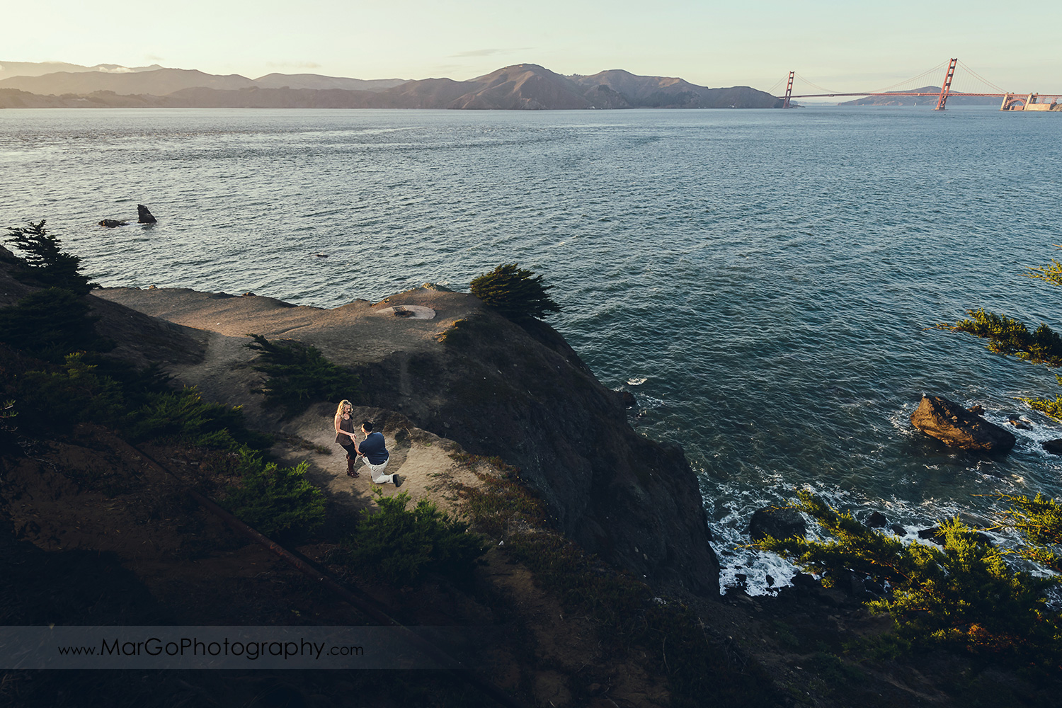 man in navy blue shirt kneeing in front of woman in brown tunic with Golden Gate Bridge in the background during engagement session at San Francisco Lands End
