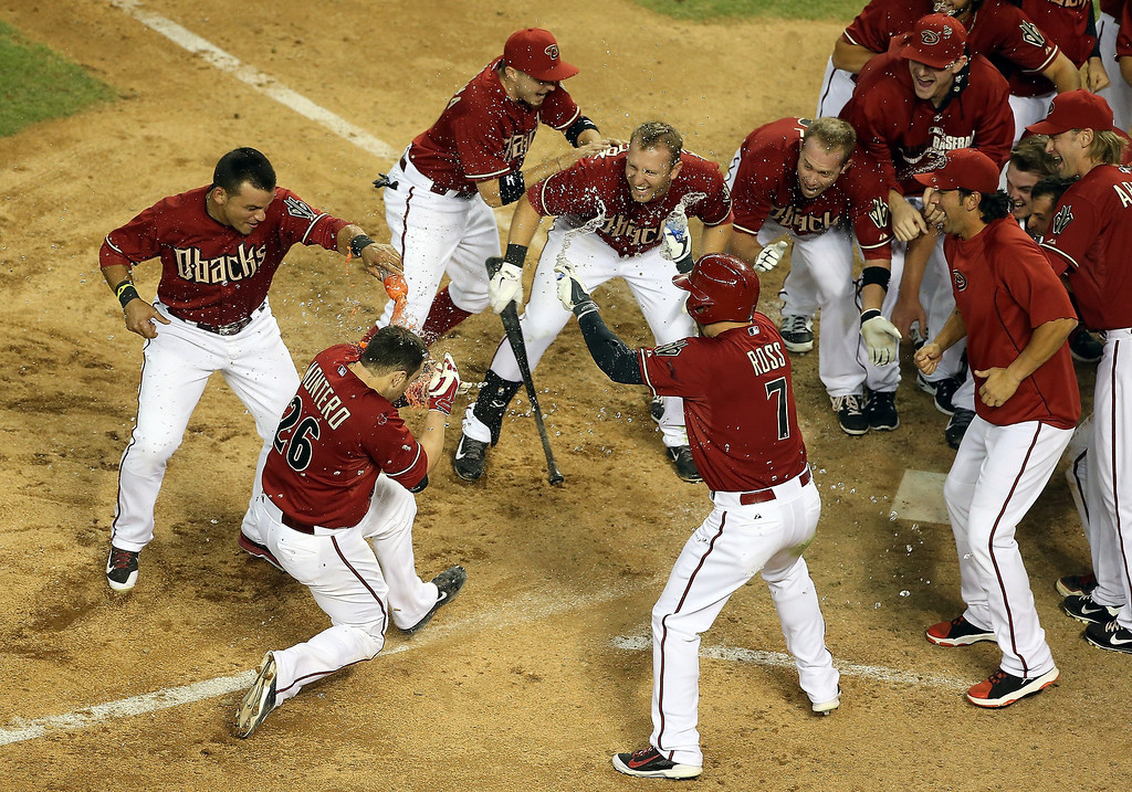. Miguel Montero #26 of the Arizona Diamondbacks is congratulated by teammates after hitting a walk off solo home-run against the Colorado Rockies in the MLB game at Chase Field on April 30, 2014 in Phoenix, Arizona.  The Diamodbacks defeated the Rockies 5-4 in 10 innings.  (Photo by Christian Petersen/Getty Images)