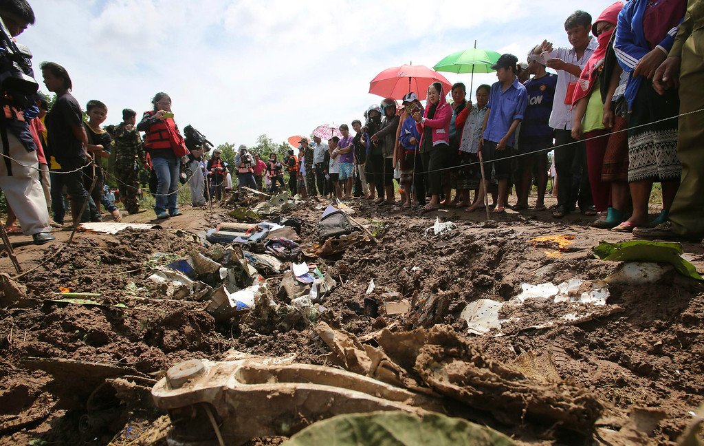 . People look at the debris of a Lao Airlines turboprop plane that crashed into the Mekong River, in Pakse, Laos on Thursday, Oct. 17, 2013.  (AP Photo/Sakchai Lalit)