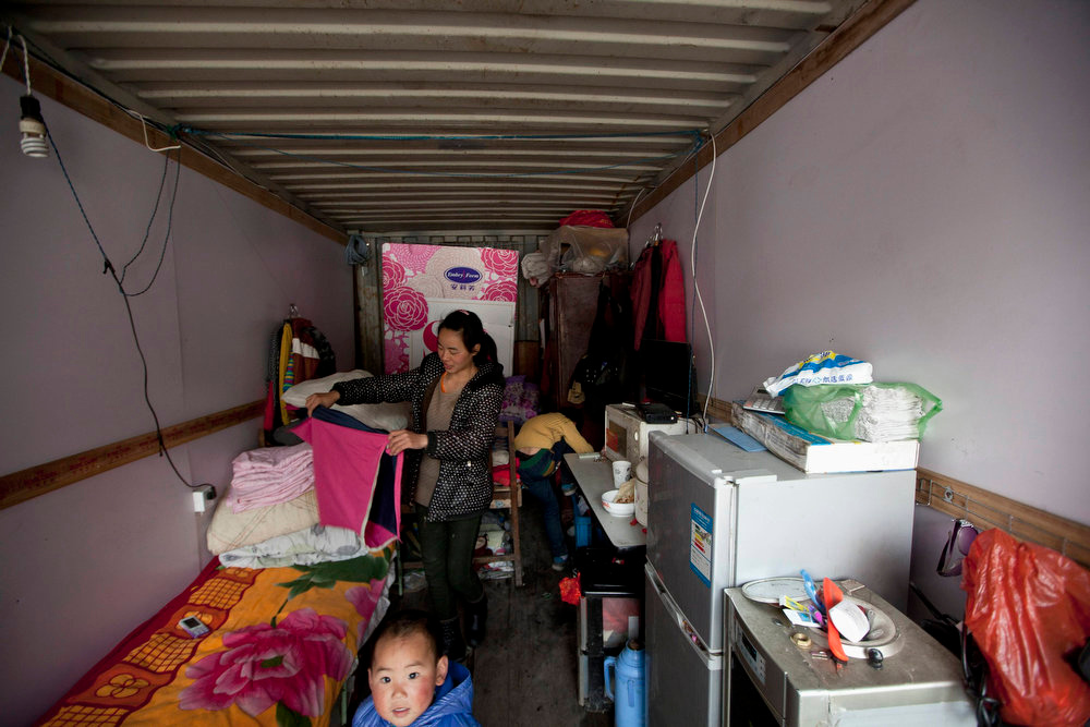 . A mother and her child are seen inside a shipping container serving as their accommodation, in Shanghai March 4, 2013.  The containers, which house different families, were set up by the landlord, who charges a rent of 500 yuan ($ 80) per month for each container. REUTERS/Aly Song
