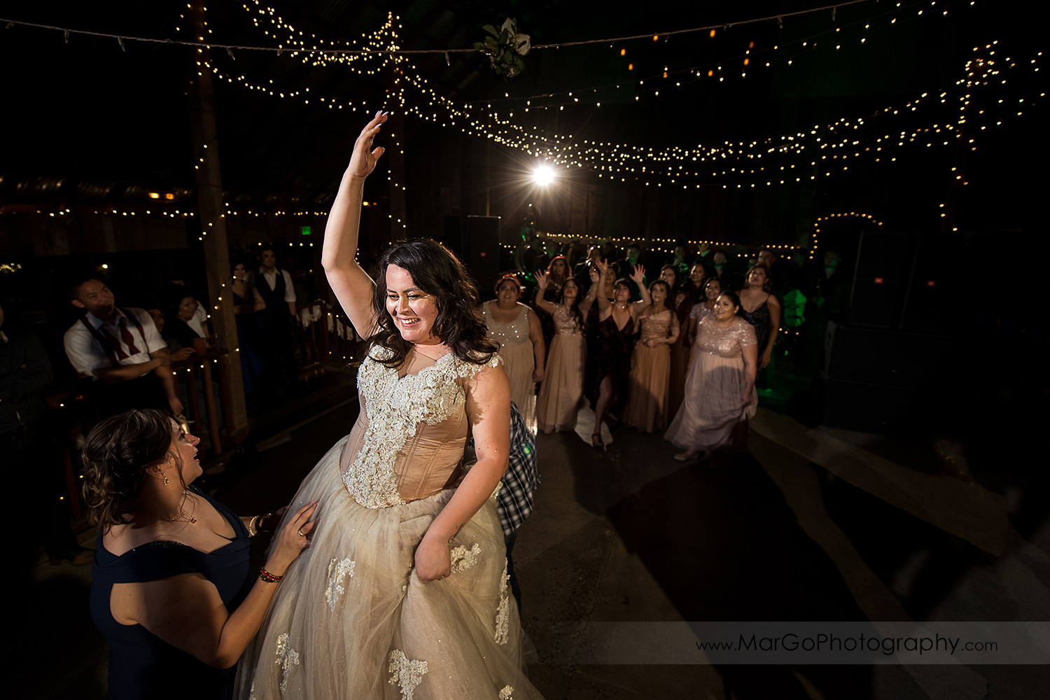 bride tossing the bouquet during mexican wedding reception at Taber Ranch Vineyards