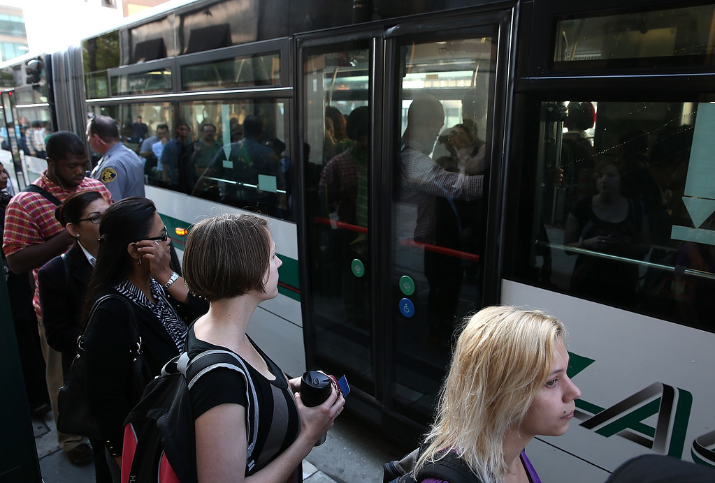 . Commuters line up as they wait to board an AC Transit bus on July 1, 2013 in Oakland, California. (Photo by Justin Sullivan/Getty Images)