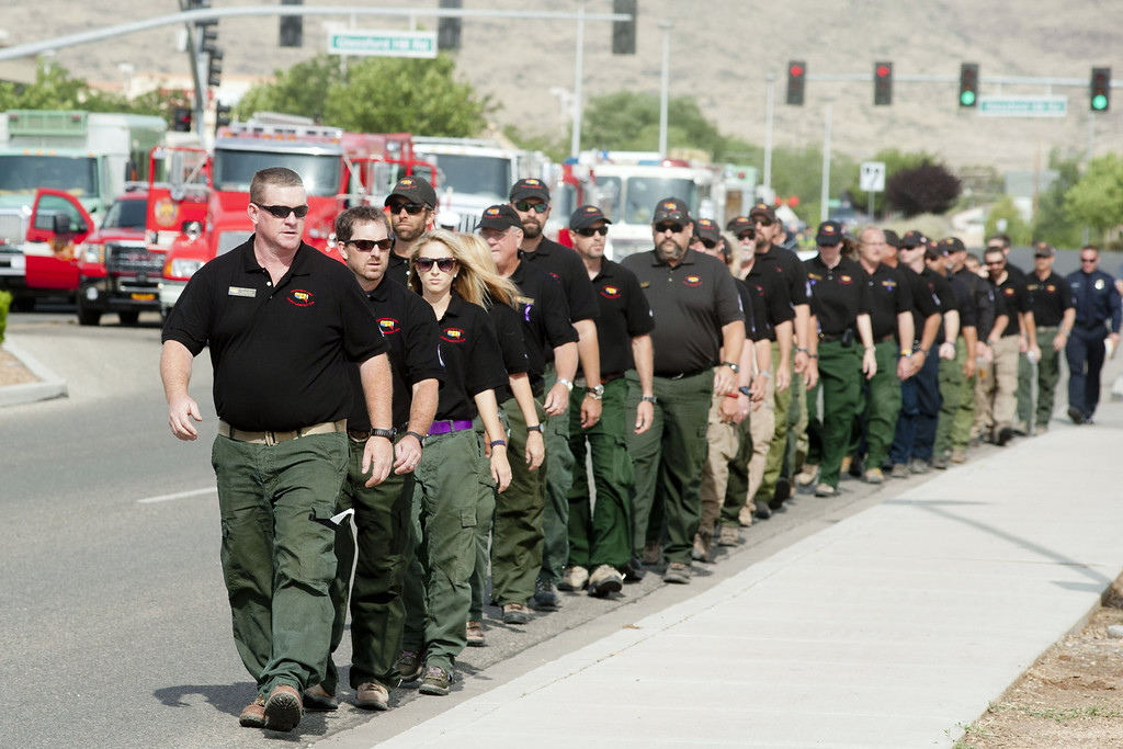 . Members of the Southwest Area Incident Management Team walk to the memorial service honoring the 19 firefighters killed in a wildfire at Tim\'s Toyota Center July 9, 2013 in Prescott Valley, Arizona. (Photo by Laura Segall/Getty Images)